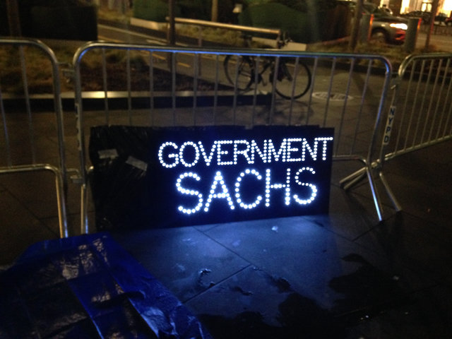 Protesters Are Camping Outside Goldman Sachs HQ Wearing Swamp Monster Masks