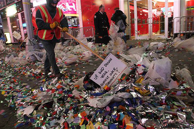 Photograph of a sanitation worker sweeping up New Year's celebration trash